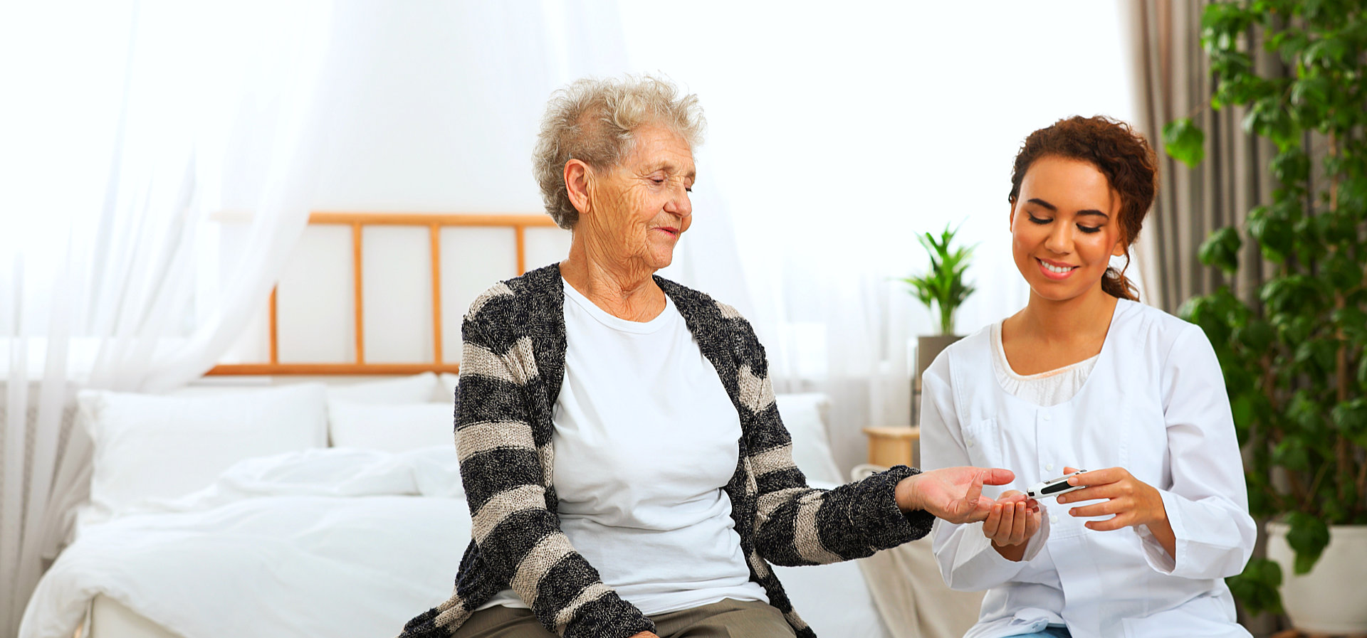caregiver cutting senior woman's nails