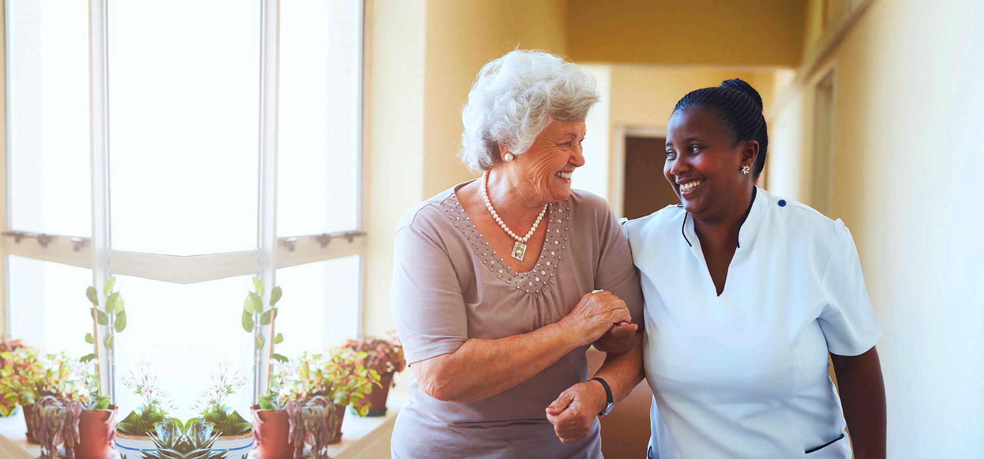 senior woman walking with caregiver