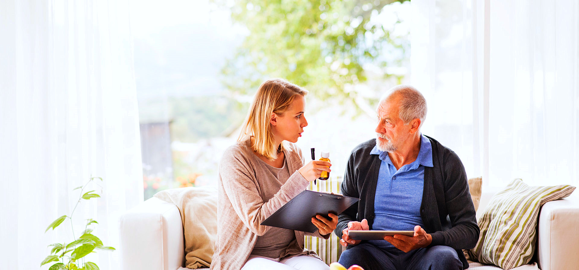 caregiver reminding senior man with his medicine