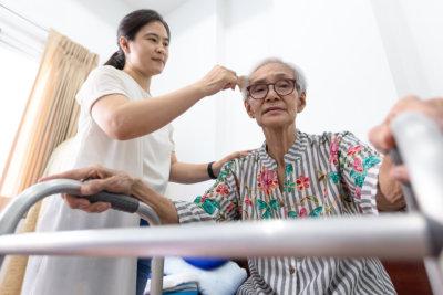 caregiver combing senior woman's hair
