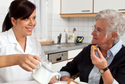 caregiver and senior woman having a meal