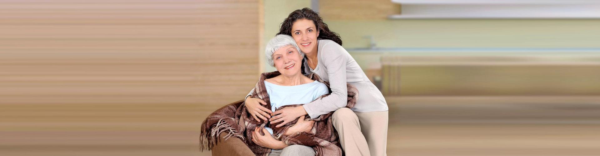 caregiver hugging senior woman