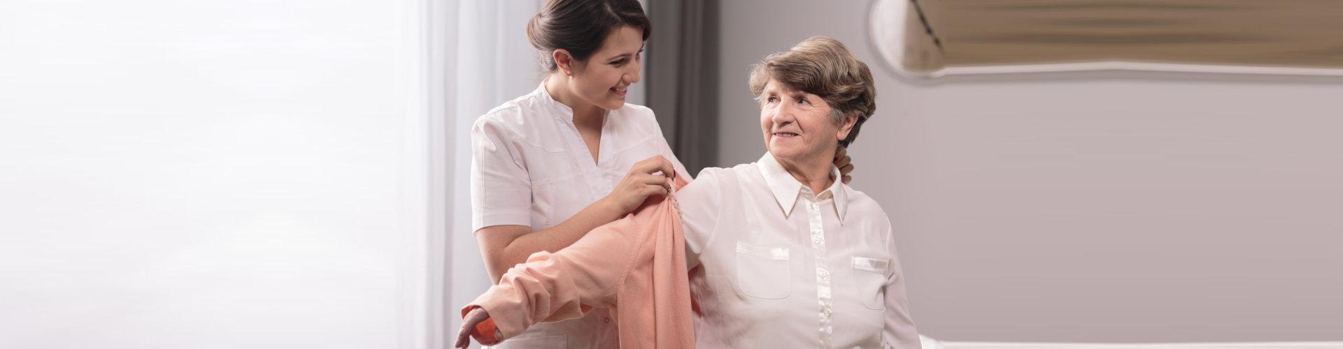 caregiver helping senior woman get dressed